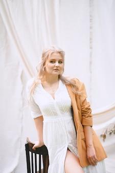 Шикарная женщина стоя и смотря в саде с белой стеной в белом платье и коричневой куртке во время дневного времени.