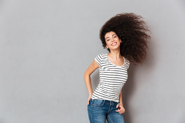 Gorgeous woman in striped t shirt having fun with waving her beautiful hair smiling being joyous and happy over grey wall