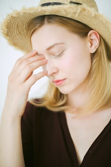 Gorgeous woman thinking and worrying in room with white background in brown shirt and sun hat.