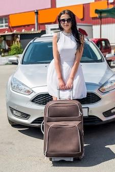 スーツケースと車でゴージャスな女性旅行者