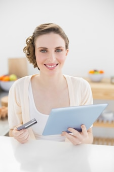 Gorgeous woman using her tablet for homeshopping sitting in her kitchen