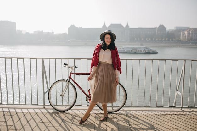 Splendida donna in abiti vintage in posa con piacere vicino al fiume