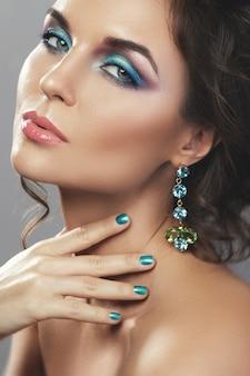 宝石で美しい高価なイヤリングを着てゴージャスな女性