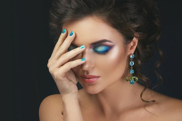 宝石で高価で美しいイヤリングを着てゴージャスな女性