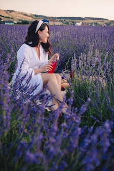 Gorgeous woman in white dress at lavender field having picnic