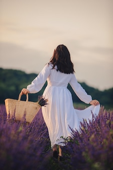 Gorgeous woman in white dress at lavender field sunset time