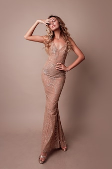 Gorgeous woman with blonde wavy hair wearing elegant beige dress