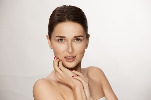 Gorgeous woman with brown hair and eyes looking to camera, copy space, beauty and cosmetic concept
