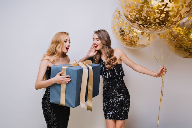 Gorgeous woman with elegant hairstyle holding big gift with surprised face expression. indoor photo of two pretty girls having fun during celebration and posing