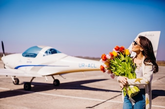 Gorgeous woman with large bouquet of tulips stands before an airplane