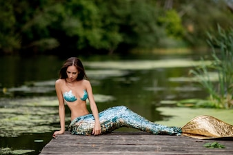 Gorgeous woman with long hair and dressed like a mermaid sits on the bridge over water