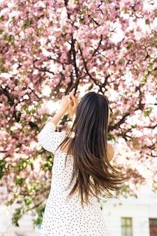 長い髪のゴージャスな女性が桜の街並み公園屋外春の花を歩いている