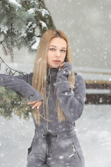 Gorgeous woman with long hair posing in the forest in snowy weather