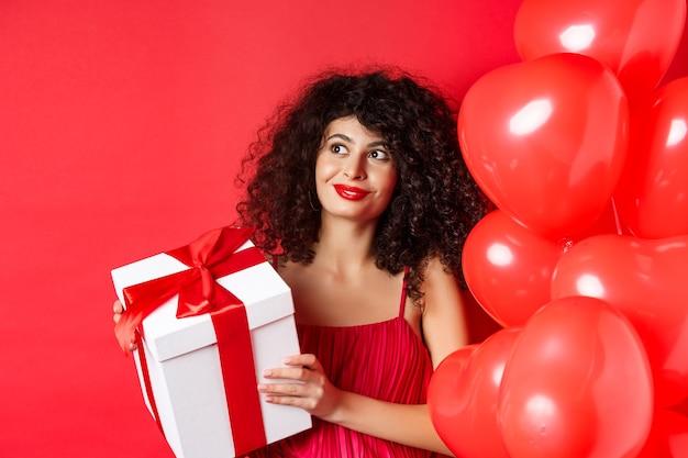 메이크업과 이브닝 드레스와 화려한 여자, 깜짝 선물을 받고 웃고, 발렌타인 데이 로맨틱 풍선 근처 빨간색 배경에 서.