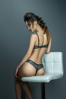 Gorgeous woman with sexual round buttocks sits on white leather chair in grey lace underwear in studio