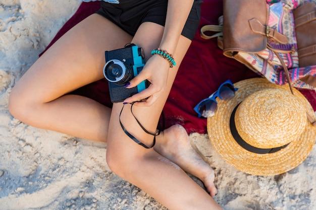 Splendida donna con corpo abbronzato, labbra rosse piene el gambe lunghe in posa sulla spiaggia soleggiata tropicale indossare top corto, pantaloncini e cappello di paglia.