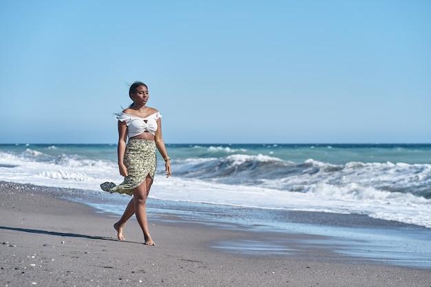 夏らしいスカートでビーチを散歩するゴージャスな若いアフリカ系アメリカ人女性