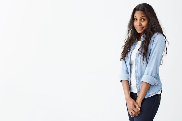Великолепная молодая афроамериканская женщина с темной чистой кожей и красивым набором черт лица, одетая в джинсовую светло-голубую рубашку на белом топе, с распущенными волнистыми волосами