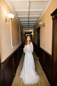 Gorgeous young asian woman in elegant dress looking at camera and window, morning of the bride, wedding