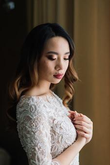 Великолепная молодая азиатская женщина в элегантном платье, смотрящая в камеру и окно, утро невесты, свадьба