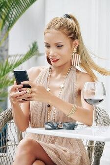Великолепная молодая блондинка азиатская женщина сидит за столом в летнем кафе и делает сообщения в социальных сетях