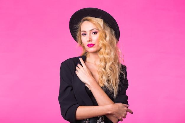 ピンクの壁にポーズをとって黒のスタイリッシュなファッショナブルな帽子のゴージャスな若いブロンドの女性。