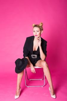 ピンクの壁にポーズをとって黒のスタイリッシュなファッショナブルな帽子を持つゴージャスな若いブロンドの女性。