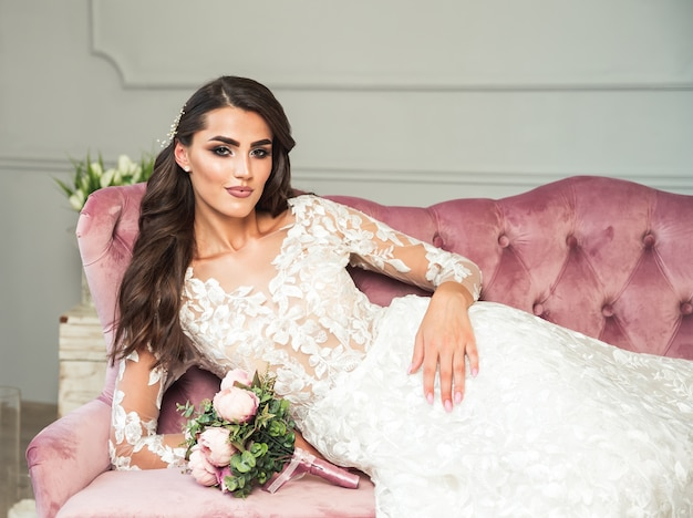 豪華な若い花嫁の肖像画。長い巻き毛の結婚式のメイク、ドレス、ジュエリーリースと美しい女性。インテリアでポーズをとるかなりブライダルのファッションモデル。官能的な女性。髪型、美容、花