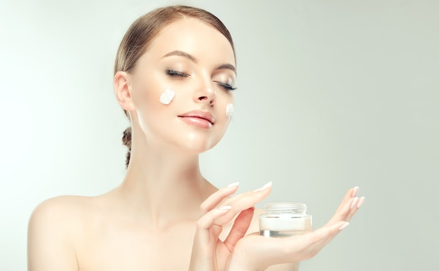 Gorgeous, young, brown haired woman with spots of cosmetic cream on the well groomed skin