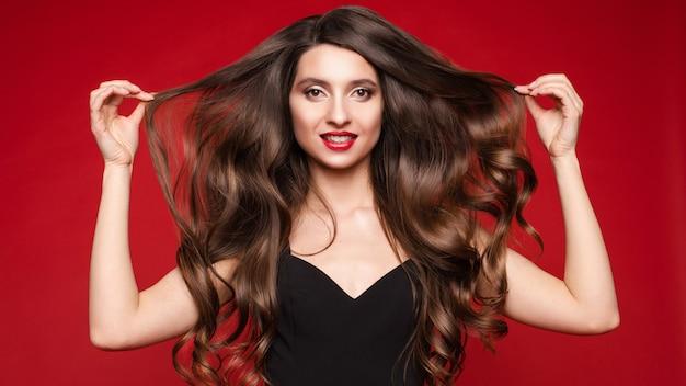 Великолепная молодая брюнетка с идеальными длинными волосами на красном фоне.