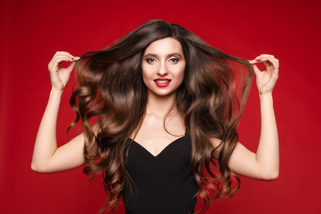 Gorgeous young brunette with ideal long hair on red background.
