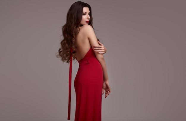 Шикарная молодая брюнетка с вьющимися волосами в красном платье