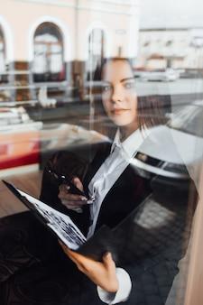 Splendida giovane donna di affari che utilizza il telefono nella caffetteria!
