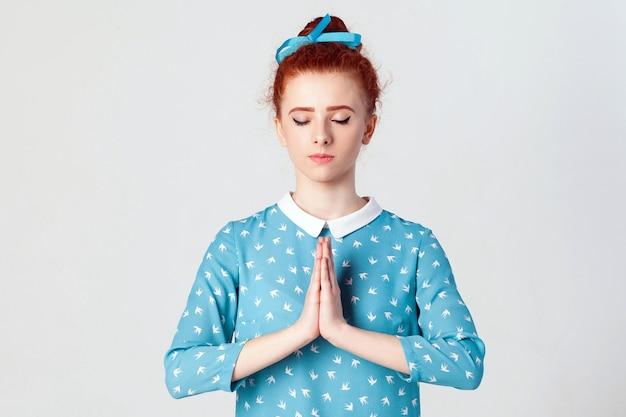화려한 젊은 백인 빨간 머리 여성, 나마스테나 기도로 손을 잡고 요가를 연습하고 집에서 혼자 명상하는 동안 눈을 감고 얼굴을 차분하게 바라보고 있습니다.
