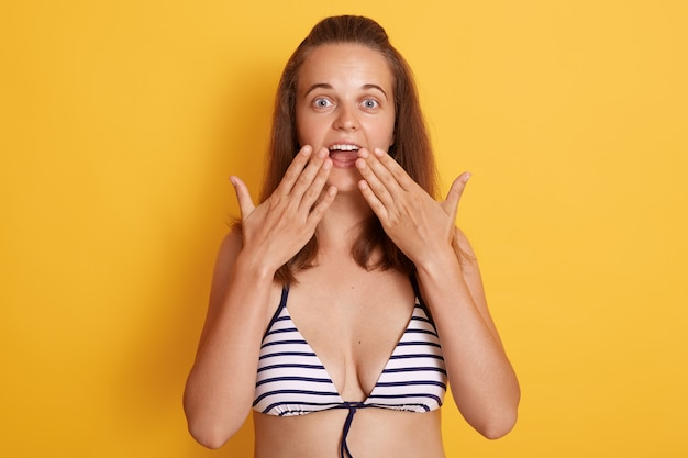 Gorgeous young dark haired woman in white and black striped swimwear with astonished facial expression, posing with widely opened mouth,covering it with palms, being surprised and excited.