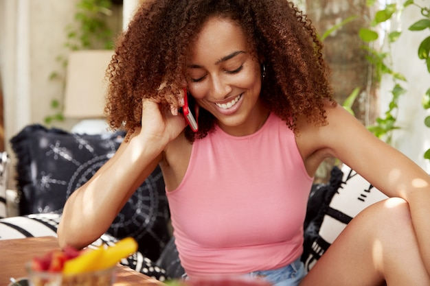 Bellissima giovane donna dalla pelle scura soddisfatta di buone notizie mentre parla al cellulare, si rallegra di vacanze indimenticabili, si sente rilassata sul divano, ama viaggiare all'estero. concetto di comunicazione
