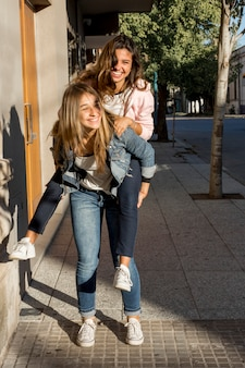 Gorgeous young girl giving piggyback to her female friend on sidewalk