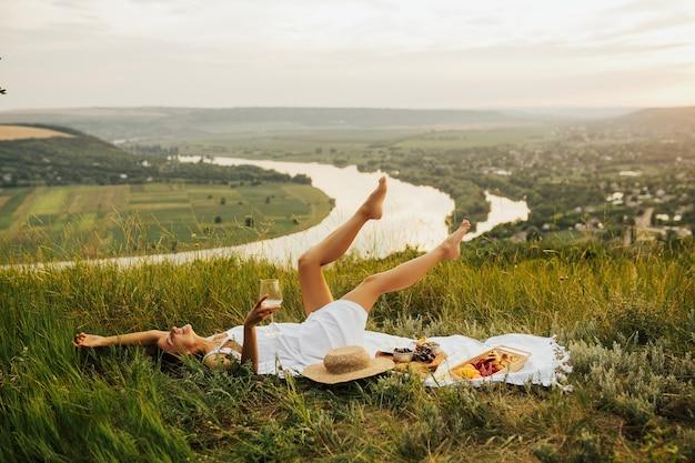 草の上に横たわって、絵のように美しい場所でピクニックをしている白いサンドレスのゴージャスな少女。