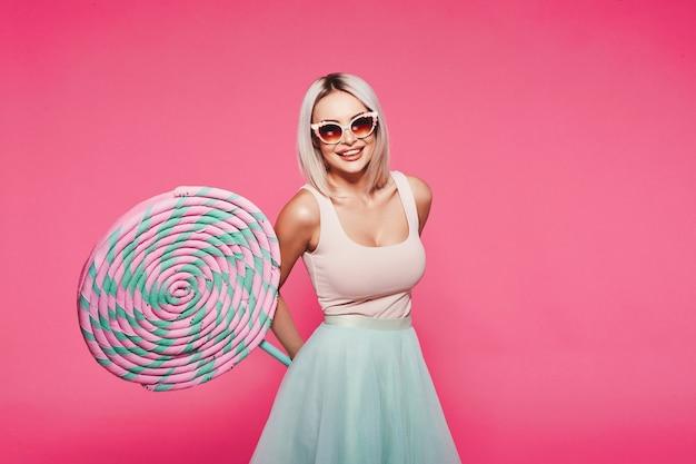 巨大な甘いロリーポップで立っているトップとスカートを身に着けているブロンドの髪を持つゴージャスな若い女の子