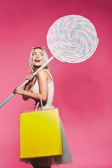 거대한 달콤한 사탕과 함께 서있는 상단과 치마를 입고 금발 머리를 가진 화려한 어린 소녀