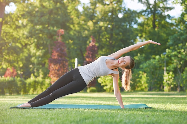 Gorgeous young happy woman smiling while doing side planking exercise outdoors in the morning park nature grass fitness healthcare concept.