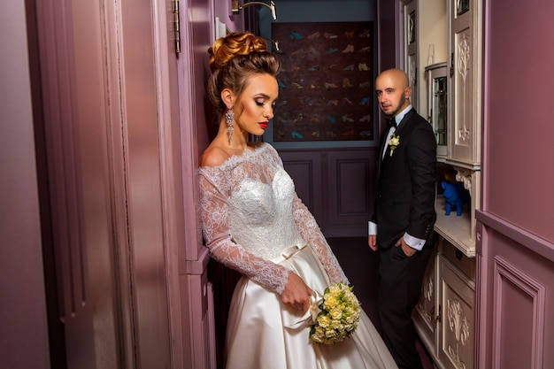 Gorgeous young just married couple posing in wedding suits