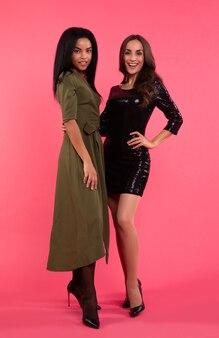 ゴージャスな若い女性が抱きしめ、カメラを見て、大きく笑っています。どちらも緑と黒のドレスを着ています。