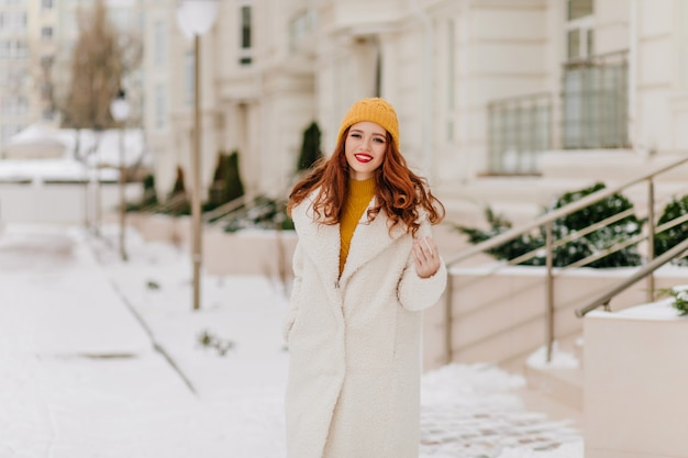 1 월에 미소로 포즈를 취하는 화려한 젊은 아가씨. 웃는 생강 여자의 겨울 초상화입니다.