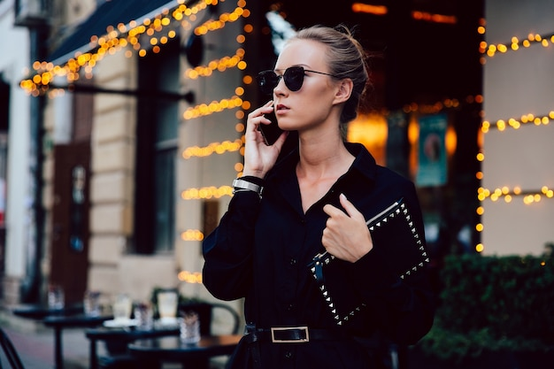 Gorgeous young lady in strict black coat talking by cell phone, wearing eyeglasses