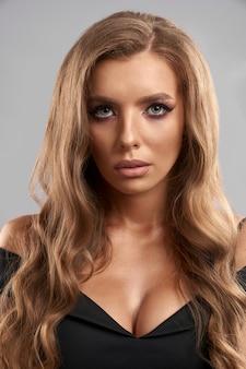 Великолепная молодая дама с длинными вьющимися волосами и вечерним макияжем позирует. понятие женской красоты и элегантности.