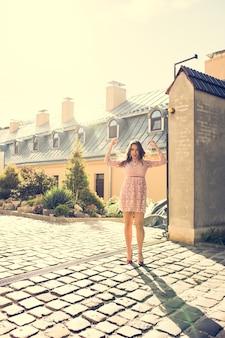 通りで太陽の光でポーズをとる透明なドレスのゴージャスな若いモデル。ヴィンテージ調色