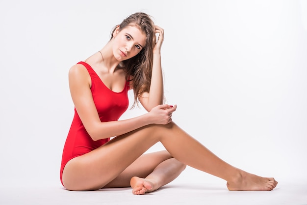 Gorgeous young model with brunette hair is sitting on the floor dressed up in red swimming suit isolated on white background