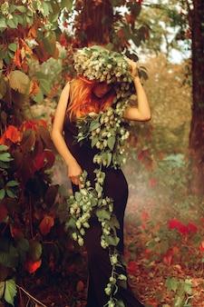 森の中で屋外でポーズをとるホップを持つゴージャスな若い赤毛の女性