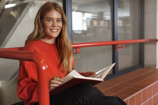 Gorgeous young redhead female student, girl sits alone and reading book, smiling camera pleased.